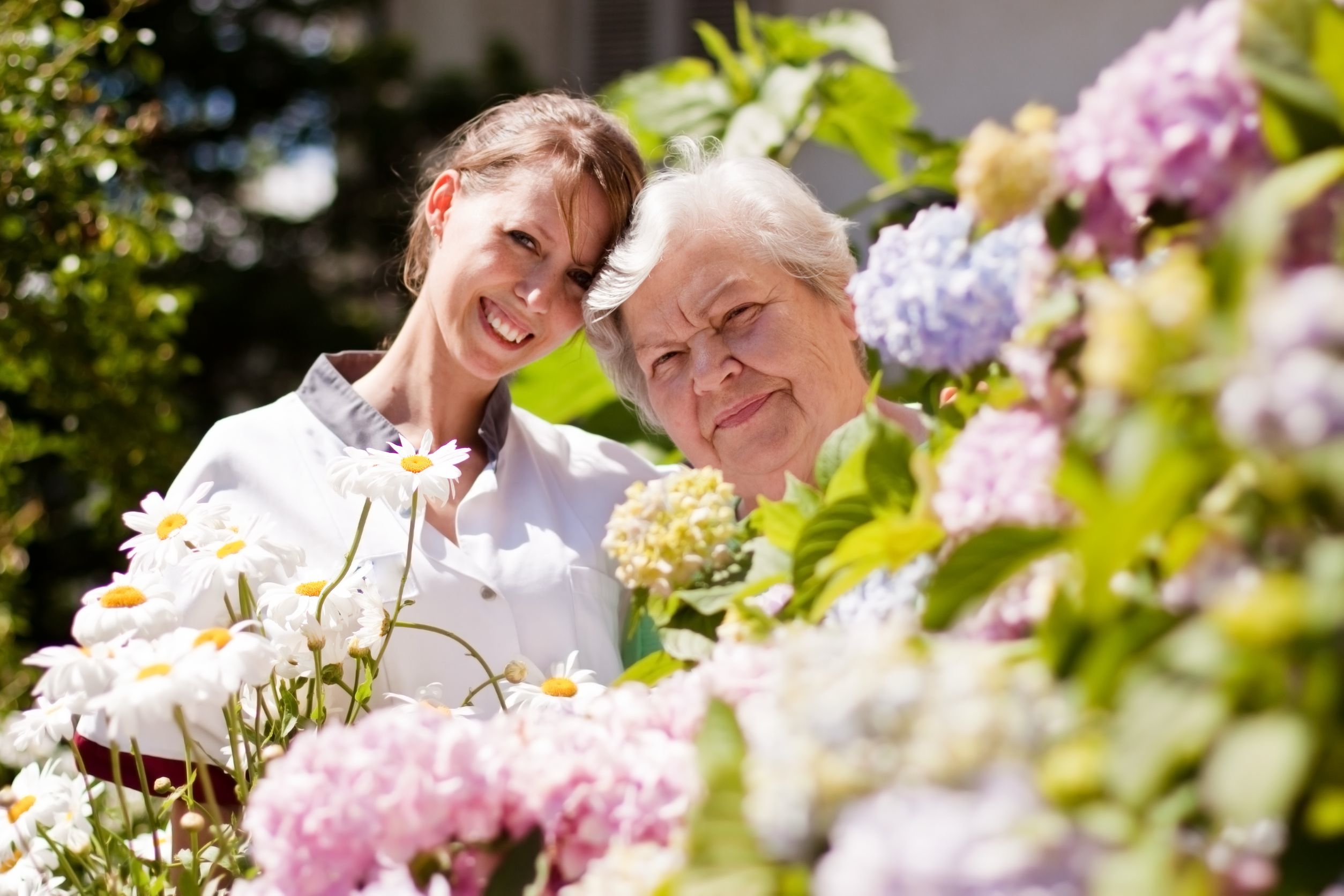 image of younger woman and older woman standing in a garden of flowers